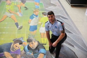 Mick Ennis kneeling on the 3d artwork of NRL players of footy ground smashing out of a television screen into the viewers loungeroom