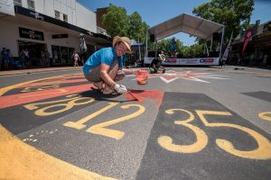 Artists creating a Roulette artwork on the ground in chalk