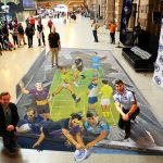 Mick Ennis, Matty Johns and Blake Austin kneeling and standing on the 3d artwork of NRL players of footy ground smashing out of a television screen into the viewers loungeroom