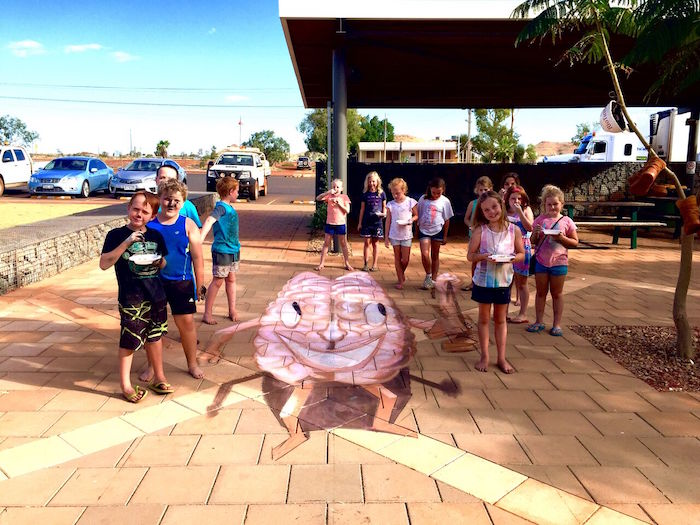 Happy kids standing around a happy brain 3D artwork in Pannawonnica