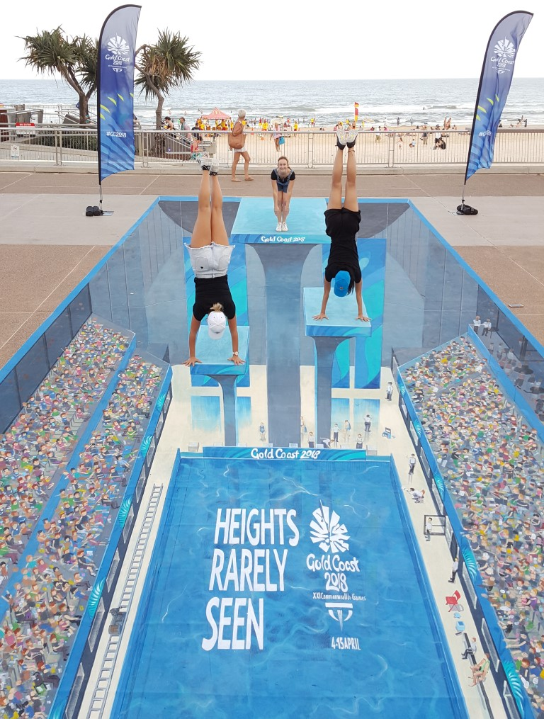 people diving into commonwealth games swimming pool