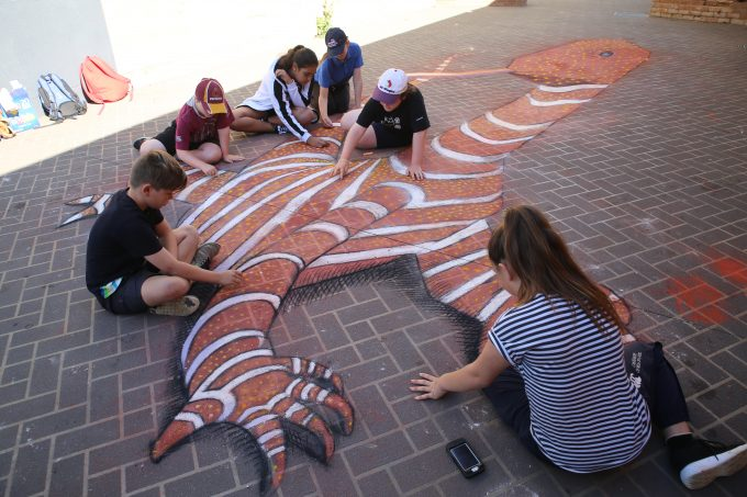 Local youth working on 3D Chalk goanna in Forbes