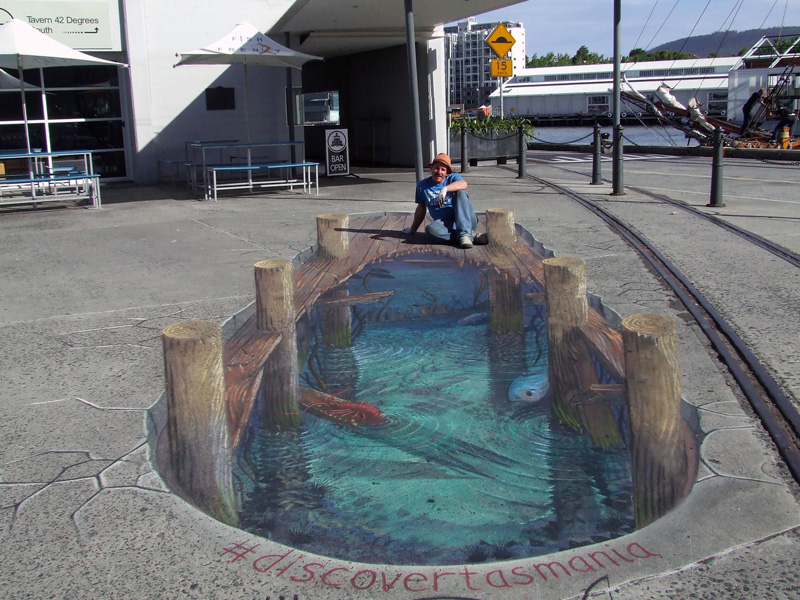 3D chalk art pier with fish swimming below