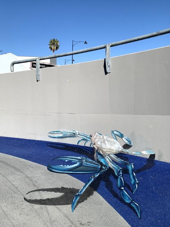 3D blue swimmer crab greets people at bridge